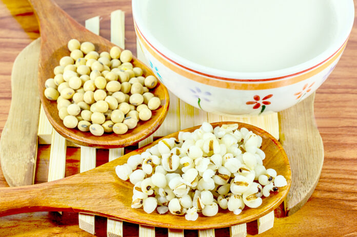 Soy milk on wooden background with soybeans or soya beans placed on side, selective focus,Healthy food