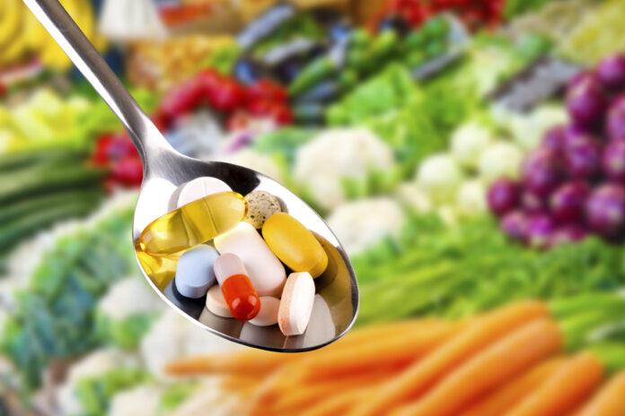 cuillère avec diverses pilules, compléments alimentaires sur fond de légumes flous.