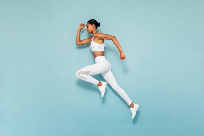 Sport Frau läuft im Studio. In voller Länge Schuss von jungen weiblichen trainiert über blauen Hintergrund.