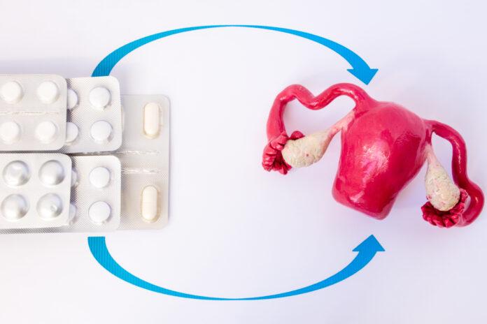 Stapelblister mit Pillen und Kapseln in spitzen Pfeilen auf Modell der Gebärmutter mit Eierstöcken. Konzeptfoto der Hormonersatztherapie in der Gynäkologie bei Menopause, Höhepunkt, entfernten Eierstöcken