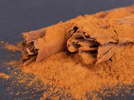 Sticks and ground ceylon cinnamon on dark background