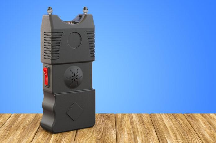 Stun Gun, electroshock weapon on the wooden table. 3D rendering
