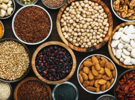 Superfoods, legumes, nuts, seeds and cereals set in bowls on wooden background. Superfood as chia, spirulina, beans, goji berries, quinoa, turmeric, mung bean, buckwheat, lentils, flax seed, wild rice and almond. Copy space, top view