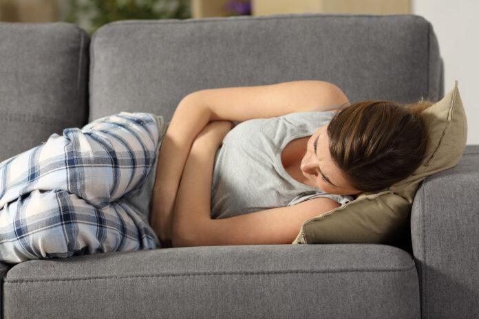 Teenager leiden Bauch pms Symptome liegen auf einem Sofa im Wohnzimmer zu Hause