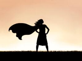 La silhouette d'une super héroïne forte et belle, coiffée d'une casquette, est isolée sur fond de coucher de soleil dans le ciel.