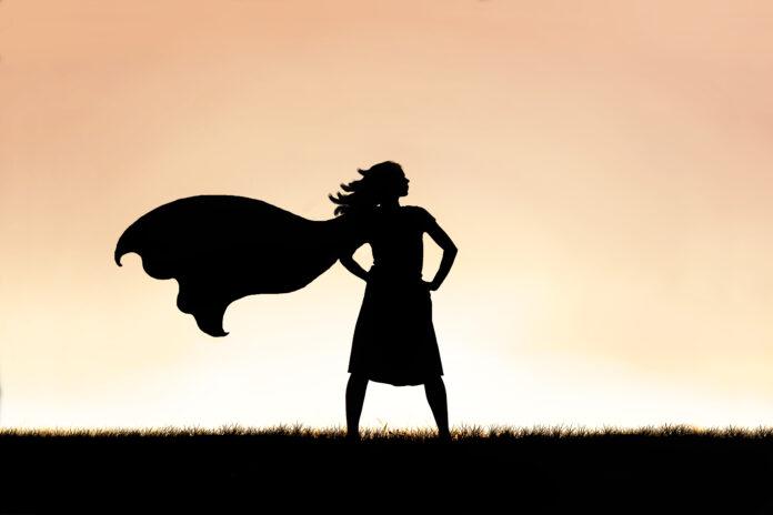 Die Silhouette eines starken, schönen caped Superheld Frau steht isoliert gegen einen Sonnenuntergang in den Himmel Hintergrund.