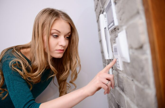 The woman entering code into the keypad of the alarm system and activates the alarm
