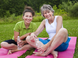 Two mature ladies share a laugh after yoga class.