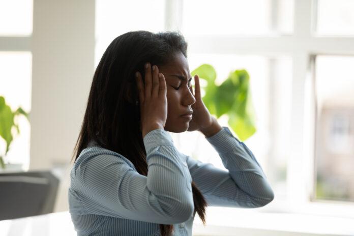 Unglückliche afroamerikanische Geschäftsfrau leidet unter Kopfschmerzen bei der Arbeit am Laptop. Diverse weibliche Mitarbeiter stressig berühren Schläfen halten Kopf denken über Business-Problem.