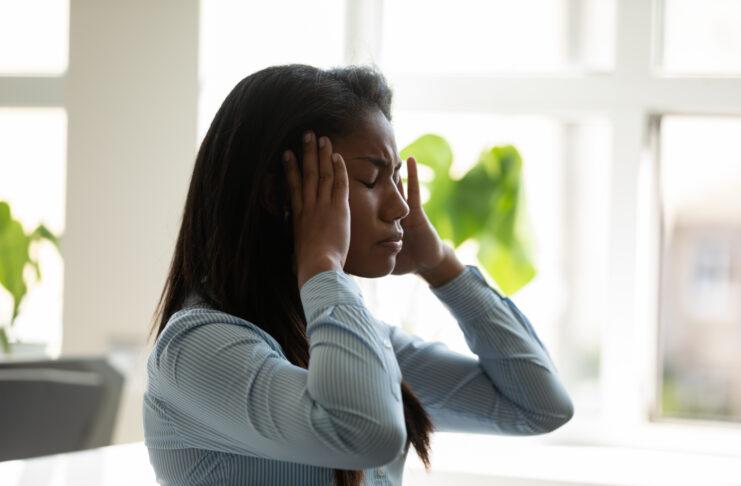 Ongelukkige afrikaanse amerikaanse onderneemster die aan hoofdpijn op het werk aan laptop lijdt. Diverse vrouwelijke werknemer beklemtonend het raken van tempels houdend hoofd denkend over bedrijfsprobleem.