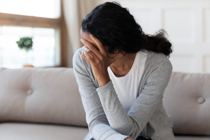 Unhappy biracial young woman sit on couch at home look in distance feel depressed sad, upset African American female lost in thoughts, suffer from miscarriage or abortion, psychological help concept