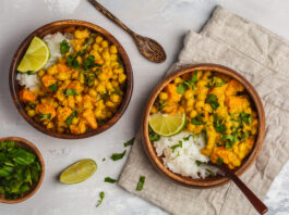 Vegan Sweet Potato Chickpea curry in wooden bowl on a light background, top view, copy space. Healthy vegetarian food concept.