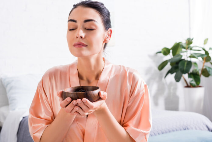 woman in silk bathrobe with wooden bowl in hands having tea ceremony in morning at home