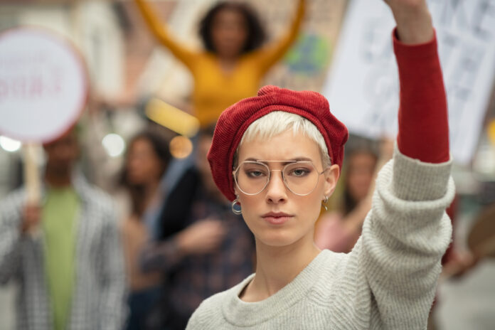 Woman leading a group of demonstrators on road for women rights. Young strong woman protest during a global strike. Portrait of angry girl in rally to protest on climate change looking at camera.