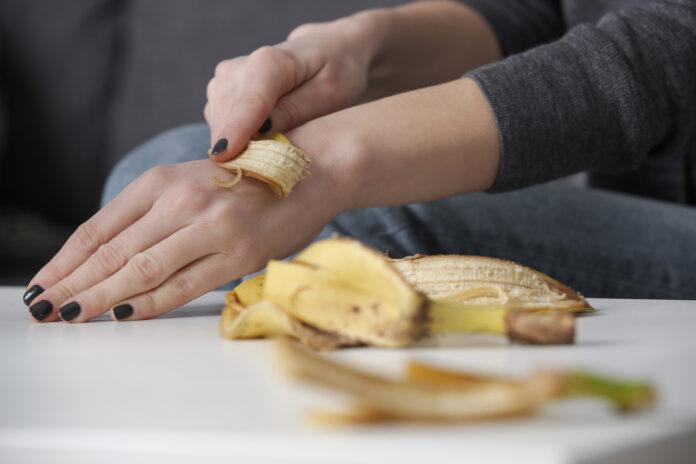 Frau reibt Bananenschalen auf ihre Hände, um die Haut zu hydratisieren. Null Abfall und natürliches Hautpflegekonzept.