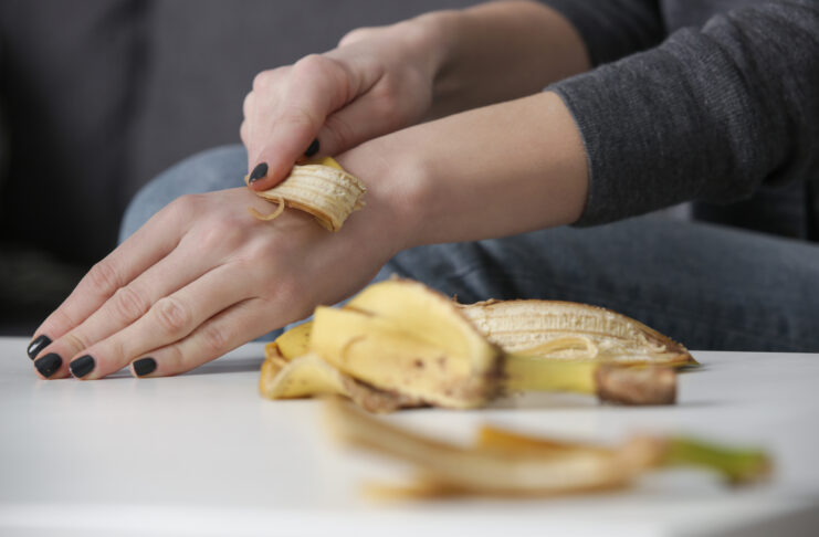 Woman rubbing banana peel on her hands to hydrate skin. Zero waste and natural skin care concept.