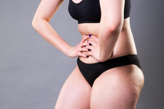 Frau mit Unterleibsschmerzen, Bauchschmerzen auf grauem Hintergrund, Studioaufnahme