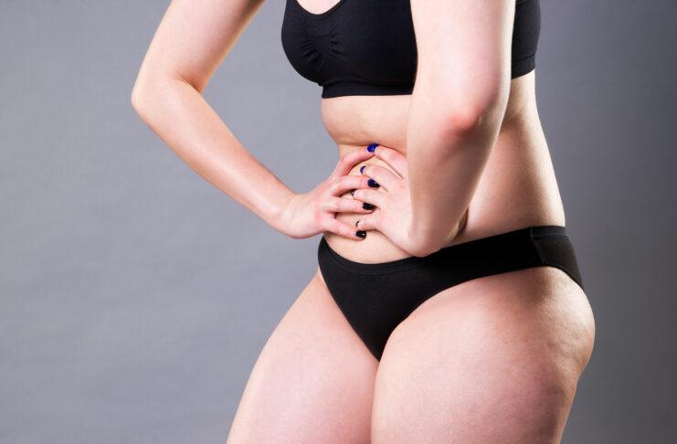 Femme souffrant de douleurs abdominales, maux d'estomac sur fond gris, photo de studio