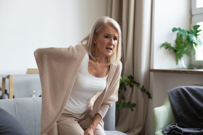 Worried upset middle aged mature woman feel hurt sudden back ache touch sore spine at home alone, tired mature senior grandmother having lower lumbago backache injury spinal pain, backpain concept