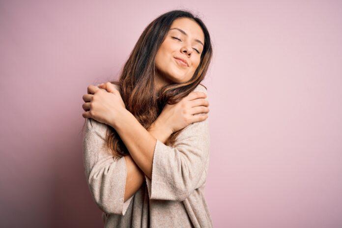 Junge schöne brünette Frau trägt lässigen Pullover stehend über rosa Hintergrund Umarmung selbst glücklich und positiv, lächelnd zuversichtlich. Selbstliebe und Selbstfürsorge