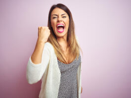 Young beautiful woman standing over pink isolated background angry and mad raising fist frustrated and furious while shouting with anger. Rage and aggressive concept.