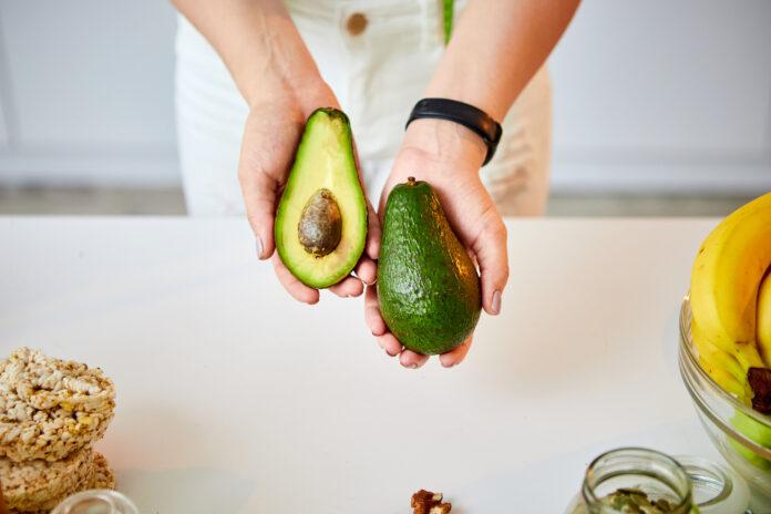 Junge glückliche Frau hält Avocado für die Herstellung von Salat in der schönen Küche mit grünen frischen Zutaten im Innenbereich. Gesundes Essen und Diät-Konzept. Gewicht zu verlieren