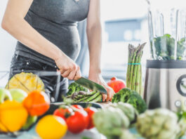 Young pregnant woman cooking healthy meal food vegetables in the kitchen. Lifestyle background. Horizontal