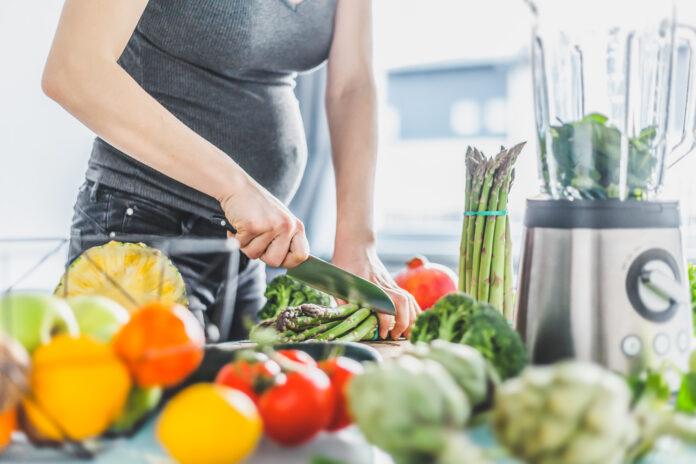 Junge schwangere Frau Kochen gesunde Mahlzeit Lebensmittel Gemüse in der Küche. Lifestyle-Hintergrund. Horizontal