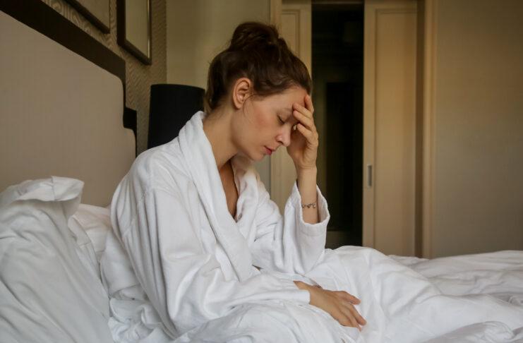 Fiatal, szomorú nő ül az ágyban, depresszió, szorongás, párkapcsolati nehézségek, migrén vagy reggeli rosszullét fogalma.