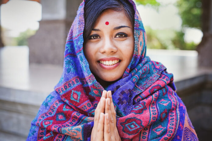 Young women in colored headscarf keepung her hands in