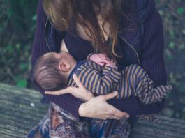 Eine junge Mutter stillt ihr Baby in einem Wald