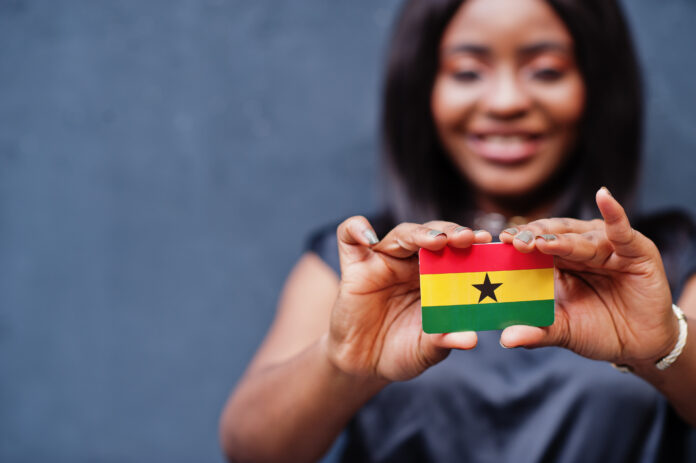 African woman hold small Ghana flag in hands.