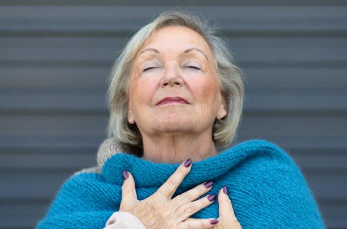 Attraktive ältere Frau genießt den Moment stehend mit geschlossenen Augen und den Kopf nach hinten geneigt mit einem heiteren Ausdruck, wie sie ihre Brust mit ihren Händen umklammert