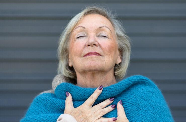 Atractiva mujer mayor saboreando el momento de pie con los ojos cerrados y la cabeza inclinada hacia atrás con una expresión de serenidad mientras se agarra el pecho con las manos