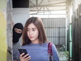Belle jeune femme tenant un smartphone et harcelée par un homme criminel avec un couteau.