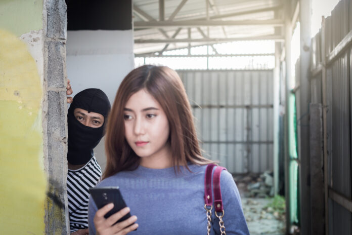 Beautiful young woman holding smartphone and being stalked by man criminal with the knife