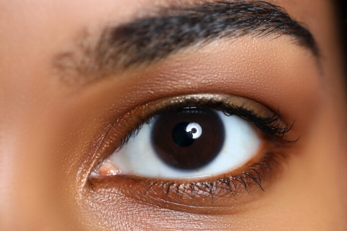 Black woman wide opened left eye close-up