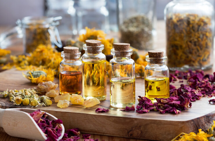 Bottles of essential oil with dried rose petals, chamomile, calendula and frankincense resin on a wooden table