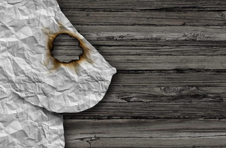 Cáncer de mama concepto médico como un símbolo de tumor de la glándula mamaria como un síntoma de crecimiento canceroso y el diagnóstico en una anatomía femenina hecha de papel arrugado abstracto en la madera con un agujero quemado como un bulto maligno o masa en un estilo de ilustración 3D.