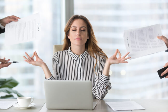 Calm female executive meditating taking break at work for mental balance, mindful businesswoman feeling relief and no stress doing yoga at work ignoring avoiding stressful job and paperwork in office