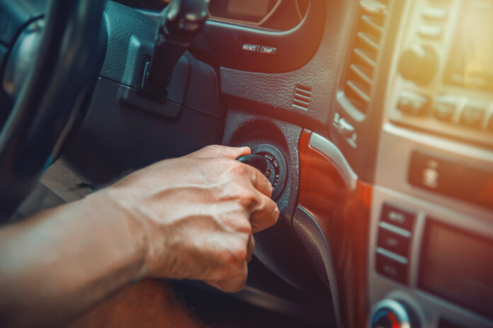 Close up of a man's hand on ignition key about to start an suv