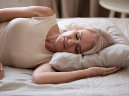 Close up of calm senior woman lying on side sleeping peacefully in comfortable bed soft pillow, tired elderly female or grandmother rest fall asleep taking nap in cozy bedroom, relaxation concept