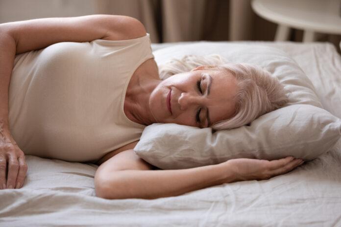 Близък план на спокойна възрастна жена, лежаща настрани, която спи спокойно в удобно легло с мека възглавница, уморена възрастна жена или баба почива, заспивайки, като подремва в уютна спалня, концепция за релаксация