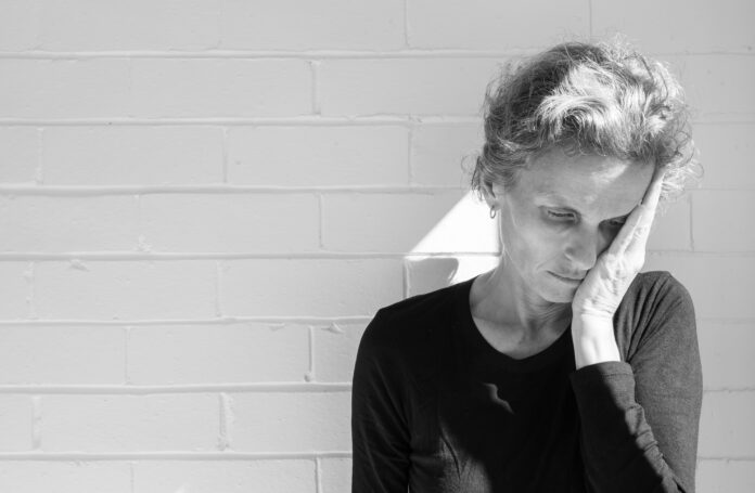 Close up of depressed older woman with hand over face - grief concept (black and white)