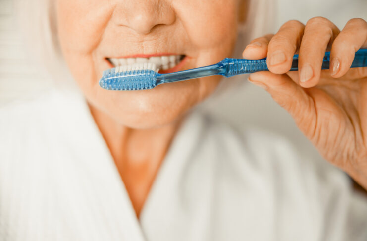 Close up of elderly lady cleaning teeth with toothbrush stock photo