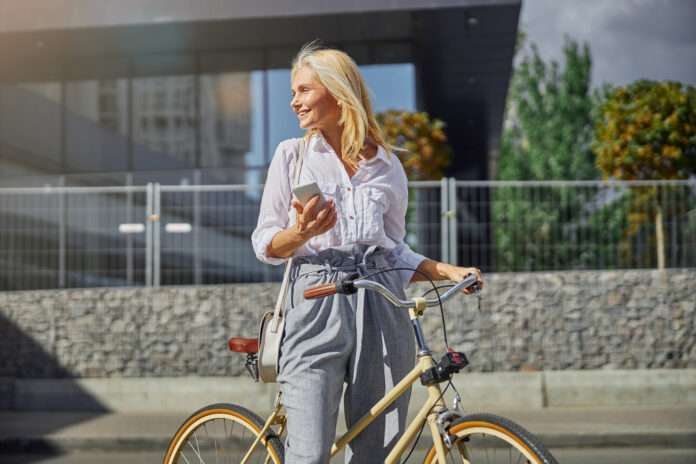 Close up portrait of attractive smiling woman in white blouse and grey pants looking away while standing with her bike in the city street