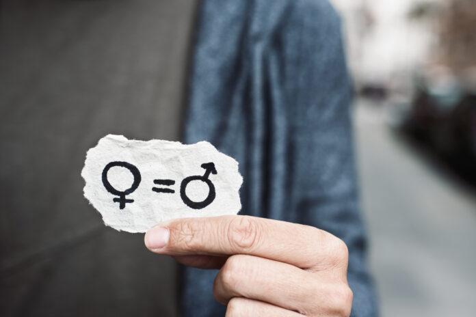 Nahaufnahme einer kaukasischen Person auf der Straße, die ein Stück Papier mit der Darstellung der Gleichberechtigung der Geschlechter eingezeichnet zeigt