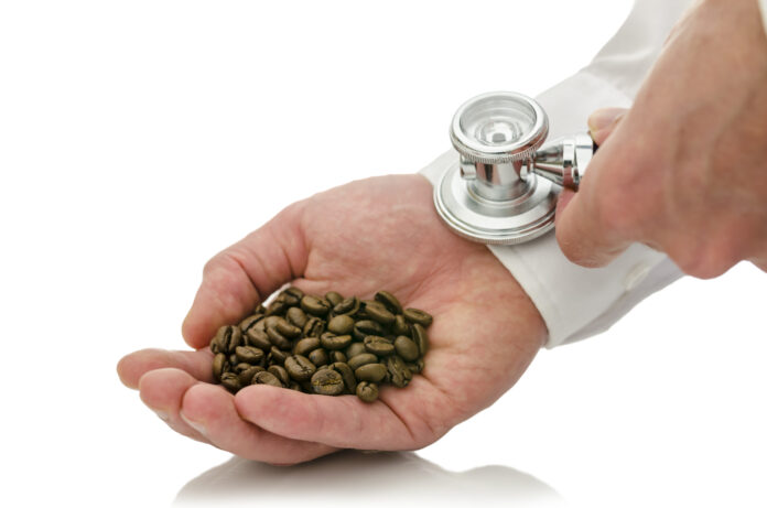 Closeup of male hand holding stethoscope on hand holding coffee grains. Isolated over white background. Concept of caffeine addiction.