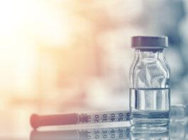 Closeup of medicine vial or flu, measles vaccine bottle with syringe and needle for immunization on vintage medical background, medicine and drug concept