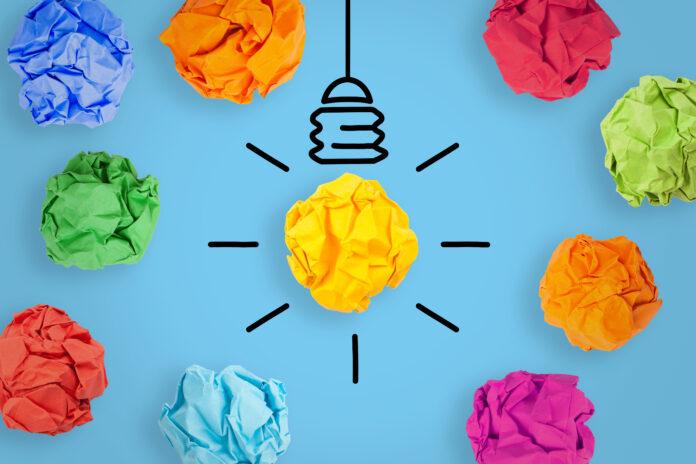 Concepts d'idées créatives avec ampoule électrique papier froissé sur fond bleu